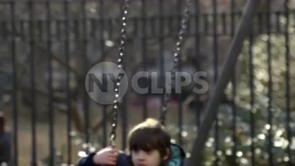 close-up of boy and girl swinging in playground, kids on swings in slow motion, tired children hanging out in Washington Square Park in 4K and 1080 HD in NYC
