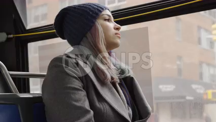pretty woman in hat and coat riding bus looking out window in winter through city in 4K - slow motion on gloomy cold day in NYC