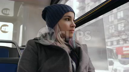 beautiful woman riding MTA bus on gloomy cold winter day - passenger looking out window in 4K NYC slow motion - contact us for model details