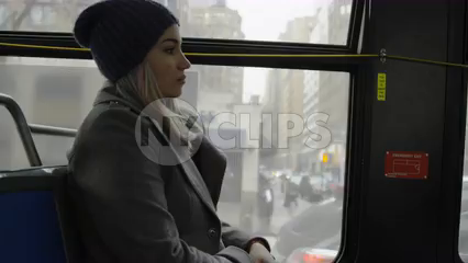 woman on bus - passenger riding MTA public transportation - hat and coat in winter on gloomy gray day  - 4K slow motion New York City