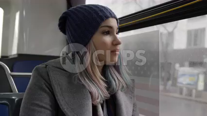 woman on moving bus - traveler commuting on MTA public transportation on depressing grey cold winter day - 4k in New York City