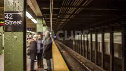 42nd Street subway station with train entering and leaving and people on crowded platform - 4K timelapse in NYC