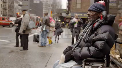 homeless man with oxygen tank in wheelchair begging for change with cup on cold winter day in Manhattan street in 4K NYC