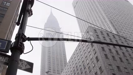 Chrysler Building in Midtown Manhattan with people crossing street on foggy day - upward angle of tall skyscraper in 4K NYC