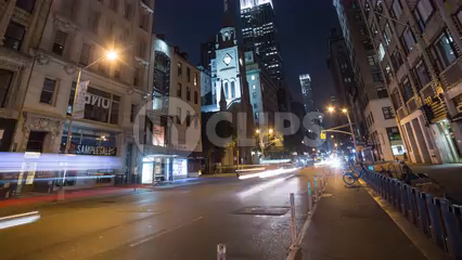 zooming out from Empire State Building lights at night with streaks of cars speeding below - 4K timelapse in Manhattan NYC