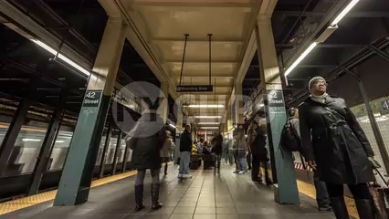 people on subway station platform at 42nd Street - trains speeding in timelapse 4K of NYC