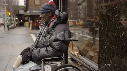 disabled homeless man in wheelchair shaking cup on cold winter day - 4k in slow motion on Manhattan street in NYC
