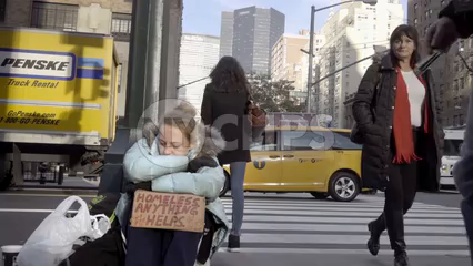 man giving homeless woman with sign a dollar and metro card on Park Ave with MetLife Building in background, Manhattan New York City