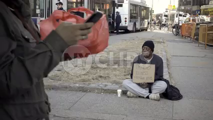 homeless African-American man with thyroid illness holding sign sitting on street, pedestrian putting change in his cup on cold fall winter day in NYC slow motion