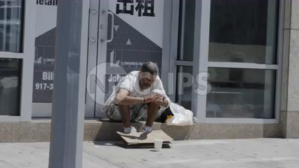 homeless man counting change on street with people walking by in 4K New York City