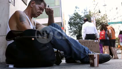 low view of homeless white veteran man sitting on sidewalk with sign and cup in Union Square Manhattan New York City
