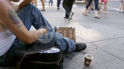 homeless man sitting on sidewalk - faceless veteran with sign and cup in Union Square Manhattan New York City