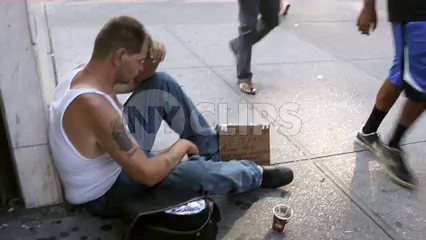 woman giving food to homeless veteran sitting on sidewalk with sign and cup in Manhattan New York City