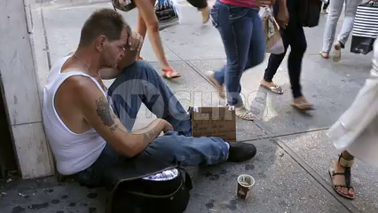 woman putting dollar in homeless veteran's cup - man sitting on sidewalk with sign - Manhattan New York City