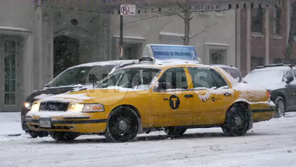 taxi cab turning corner in winter blizzard - snowing on lower 5th ave in Manhattan NYC - 4K slow motion
