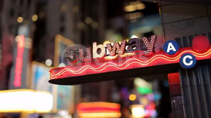 bright subway sign lights blinking near Times Square at night in New York City