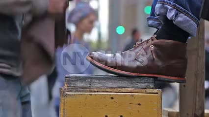 shoeshiner polishing man's boots on street - brown shoes getting polish in NYC