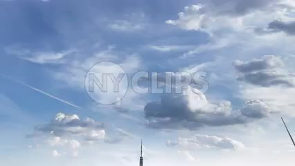 Empire State Building and Manhattan skyscrapers in cityscape tilting down quickly with clouds overhead - timelapse of NYC