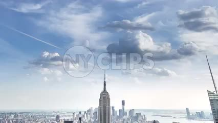 Empire State Building and Manhattan skyscrapers in cityscape tilting down from clouds overhead - day to night timelapse of NYC