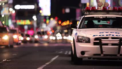 police car in Midtown Manhattan at night - Times Square lights in background with NYPD vehicle parked in NYC
