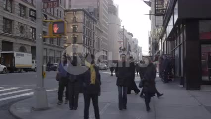taxi turning corner on 5th Ave on winter day with people walking, slow motion in NYC