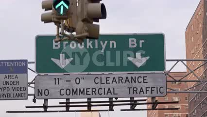close up Brooklyn Bridge sign, clearance no commercial traffic, passing underneath, green light overhead in NYC