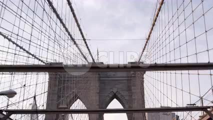 driver's first person pov driving across Brooklyn Bridge with American flag on tower in NYC