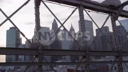 view of Manhattan skyline from inside Brooklyn Bridge, driving across landmark in NYC