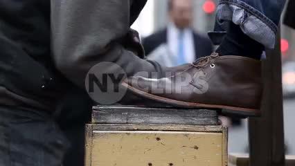 shoeshiner shining brown boots on street - close-up in NYC