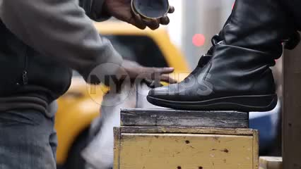 man shining woman's boots on street - shoeshiner polishing shoes in NYC