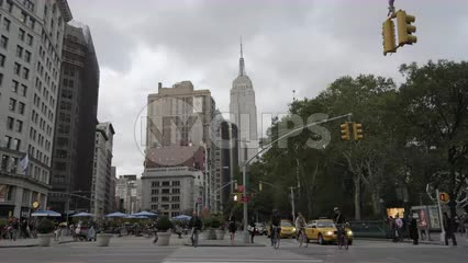 Empire State Building view from Madison Square Park on cloudy fall day with taxis and bicycles in NYC