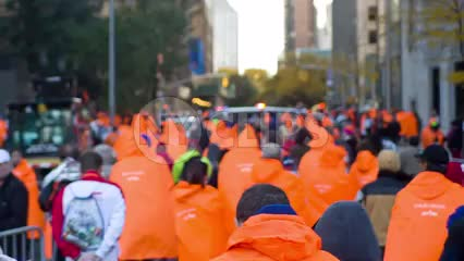 orange ponchos - people walking with backs after marathon in spring in NYC