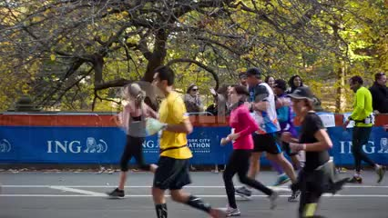 marathon runners finishing final mile in Central Park from side view with spectators onlooking in NYC