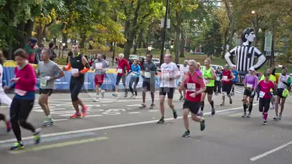 people running last mile in marathon, Central Park with Foot Locker balloon in Manhattan NYC