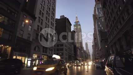 Empire State Building with colorful lights and cars in Manhattan traffic, headlights on street in early evening on Lower 5th Ave in 4K and 1080 HD in NYC