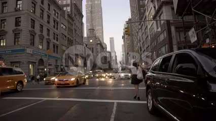 woman haling cab on 5th ave in early evening with Empire State Building lights and cars driving in rush hour traffic in summer nightlife in 4K and 1080 HD NYC
