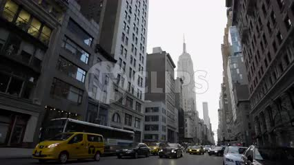 5th Ave traffic in early morning, cars and cabs driving with headlights on cloudy spring day in Manhattan with Empire State Building street view in 4K and 1080 HD in NYC