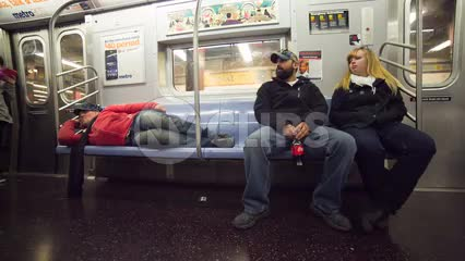 homeless man sleeping on the subway seats - low angle of tourist couple sitting on moving train in 1080 HD in NYC