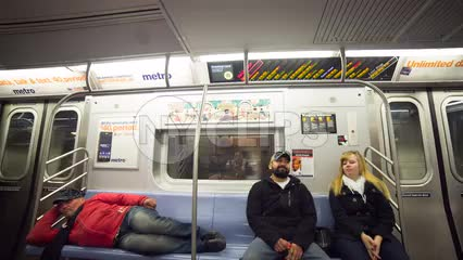man sleeping on the subway next to couple - homeless guy on moving train in 1080 HD in NYC