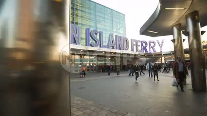 large sign for Staten Island Ferry and commuters walking at rush hour on cloudy spring or fall day in 1080 HD NYC