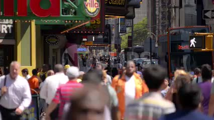 people walking with colorful jackets in Times Square on bright sunny day in summer or spring in NYC