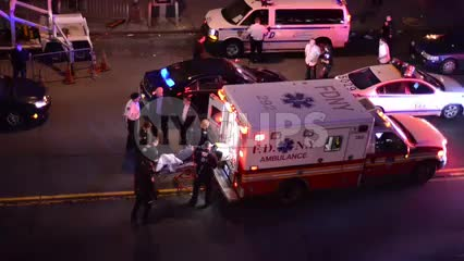 ambulance on street at night, injured person on stretcher being put into FDNY vehicle in 1080 HD in NYC