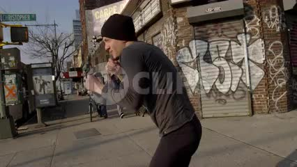 man shadow boxing in street - throwing punches on westside of Manhattan with graffiti on building