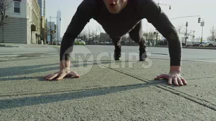man doing pushups on Manhattan's westside with Freedom Tower in background on sunny fall day