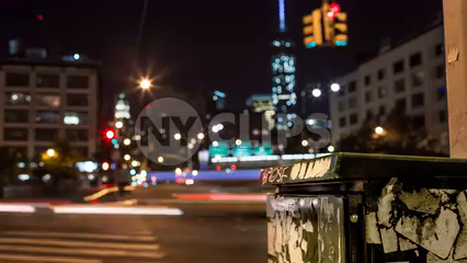 green phone box and busy intersection in Downtown Manhattan with Freedom Tower out of focus in background - 4K timelapse at night in NYC