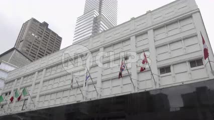 Bloomingdale's department store in Midtown Manhattan - tilting down from flags to street with cars, taxis in traffic in 4K and 1080 HD in NYC
