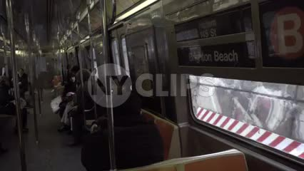panning across B train, subway with graffiti on either side of window view - passengers riding in 1080 HD in NYC