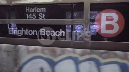 sign for B train, Harlem 145th St and Brighton Beach in Brooklyn, moving train with window, gritty New York City