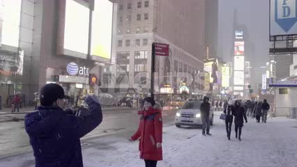 Asian man taking picture of tourist woman in winter in Times Square - snowing in 4K and 1080 HD in NYC