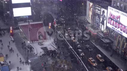 panning across snowing in Times Square from window above on high floor - winter in 4K and 1080 HD in NYC
